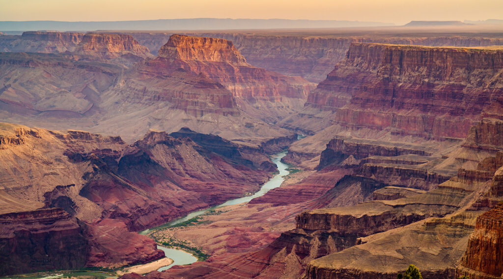Colorado river mowing between the large rocky cliffs of the Grand Canyon