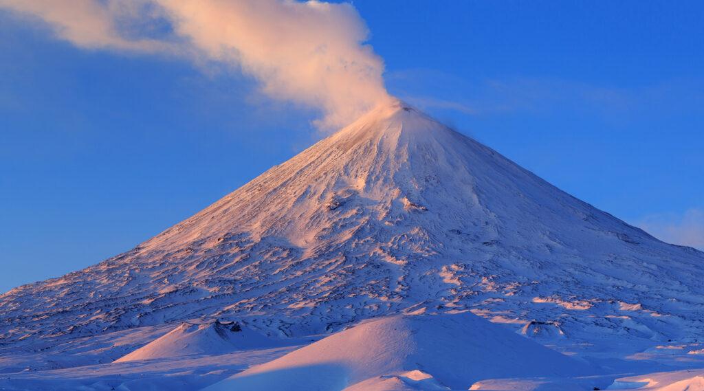 Snowy volcano of Klyuchevskaya Sopka at sunrise